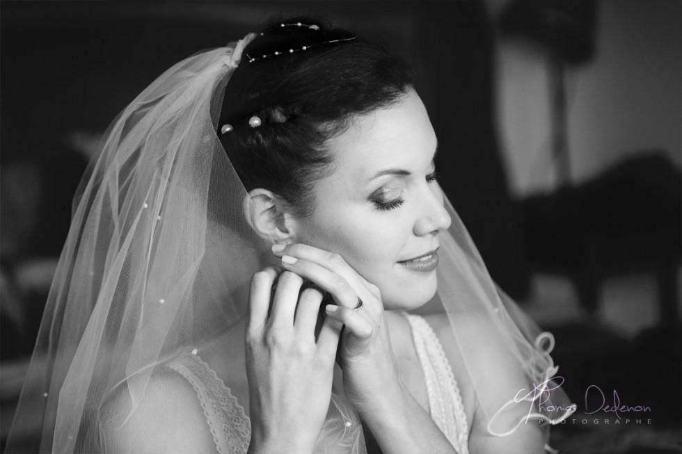 Préparatifs de la mariée qui met ses boucles d'oreilles