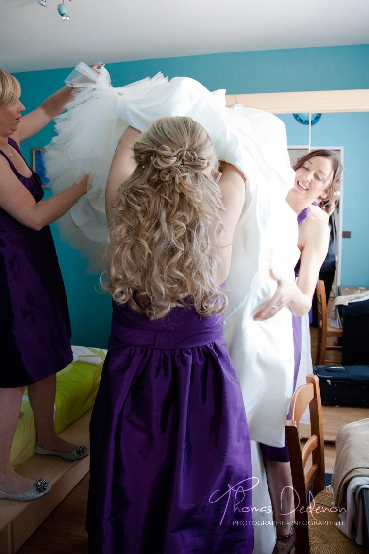Les demoiselles d'honneur aident la mariée à enfiler sa jolie robe