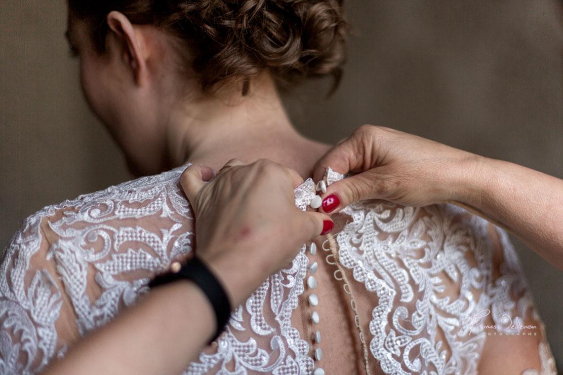 Une mère ferme la robe de mariée de sa fille