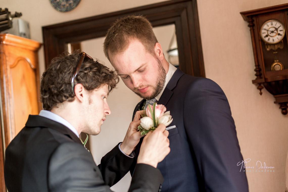 Le témoin met la boutonnière au marié
