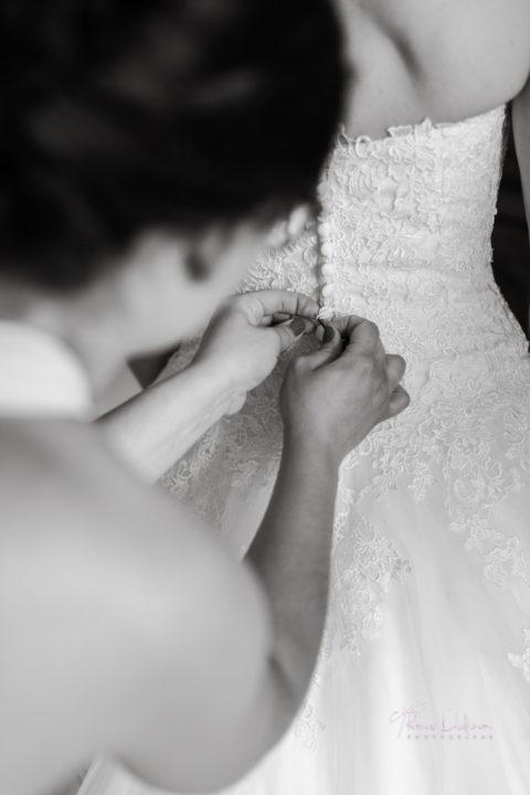 le mariée se fait aider pour mettre sa robe